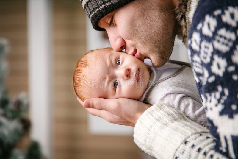生拿着和亲吻小儿子在中,当戴冬天帽子时 库存照片