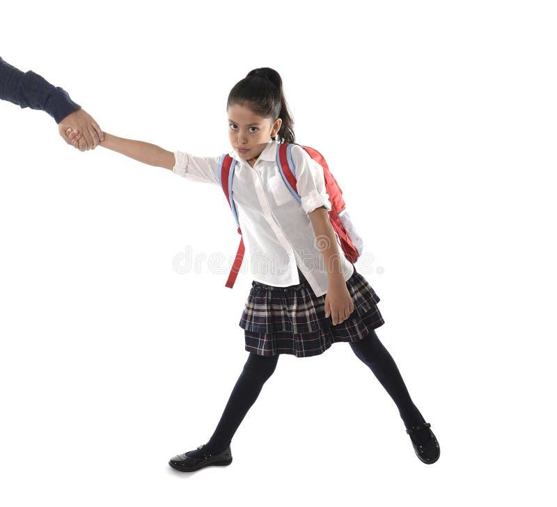 生拿着和拉扯他的有制服和背包的手年轻喜怒无常的拉丁女小学生恼怒 库存照片