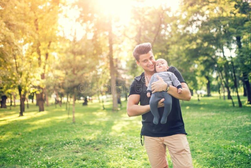 生拿着小儿子,婴儿男孩在一个晴天在公园 库存图片
