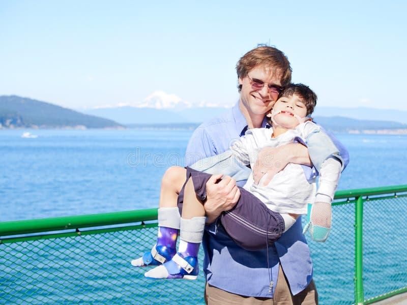 生拿着胳膊的失去能力的儿子在渡轮甲板。 免版税图库摄影