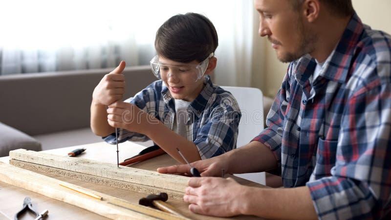 生教他微笑的儿子木匠业,使用screwer的小男孩在车间 免版税库存图片