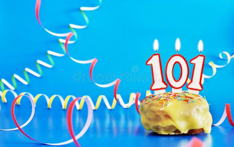 生日一百和一年 与白色灼烧的蜡烛的杯形蛋糕以第101的形式 免版税库存照片
