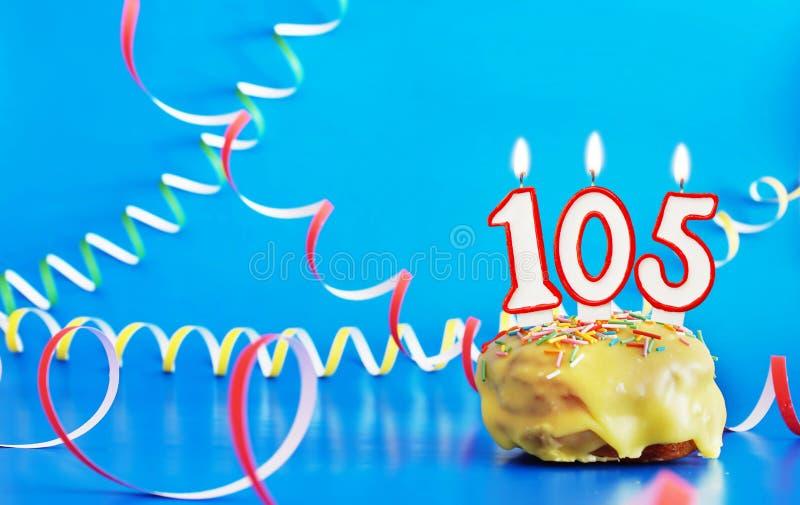 生日一百和五年 与白色灼烧的蜡烛的杯形蛋糕以第105的形式 图库摄影