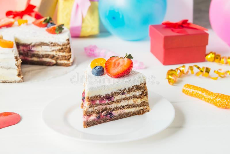 生日健康yougurt蛋糕片断用新鲜的草莓和蓝莓在欢乐背景与党装饰,礼物和 库存照片