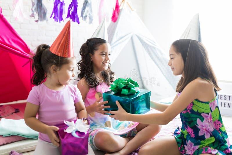 生日女孩接受当前从朋友在睡衣派对期间 免版税库存照片