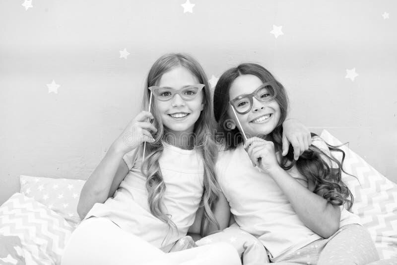 生日女孩 摆在与鬼脸照片摊支柱的孩子 睡衣派对在卧室 快乐的朋友逗人喜爱和 免版税图库摄影