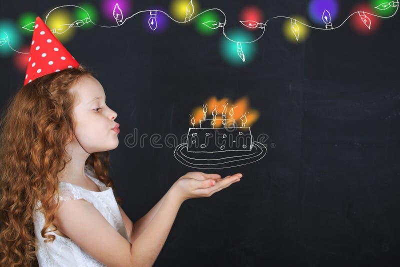生日帽子的小女孩在一个生日吹灭蜡烛 免版税库存照片