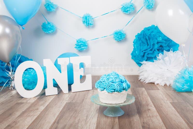 生日庆祝的欢乐背景说装饰与食家蛋糕的信件一和蓝色气球在演播室 库存图片