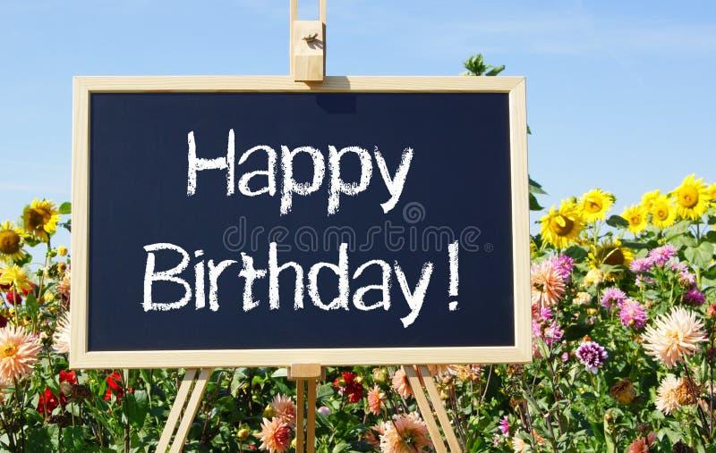 生日快乐-有文本的黑板在庭院里 库存图片