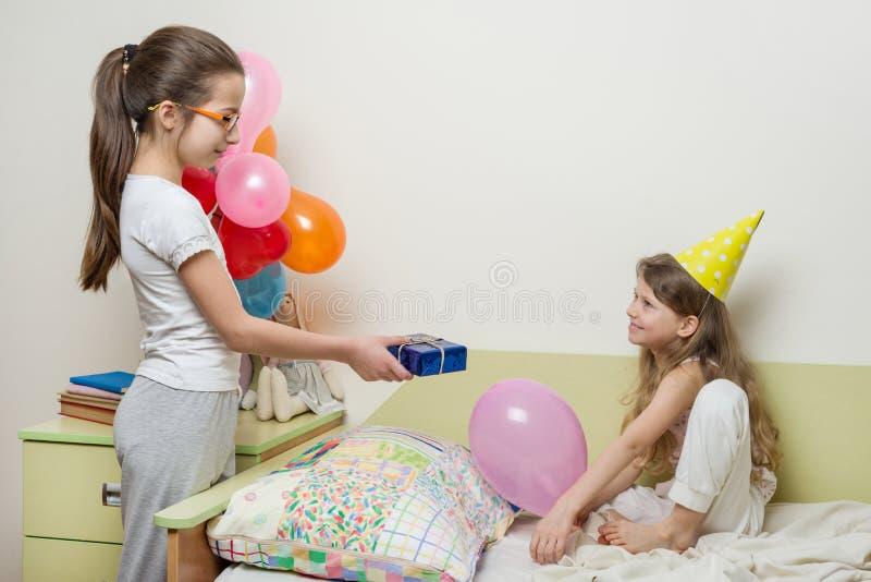 生日早晨 给惊奇礼物的更老的姐妹她逗人喜爱的妹 孩子在家在床上 免版税库存照片