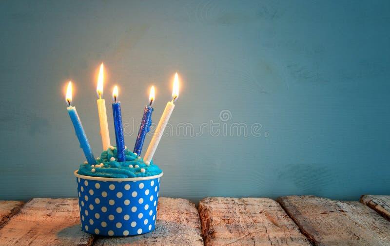 生日概念用杯形蛋糕和蜡烛在木桌上 库存照片
