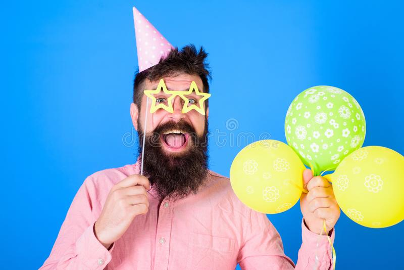 生日盖帽的愉快的有胡子的人有五颜六色的baloons和纸星状glassses的 有长的胡子的喜剧演员和 免版税库存照片