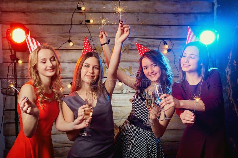 生日聚会的女孩在盖帽在他们的头和有温泉的 免版税库存照片