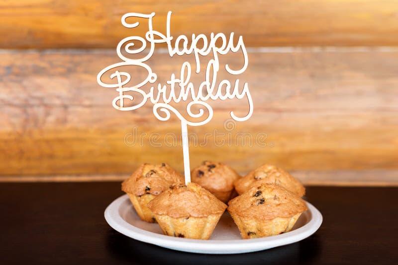生日蛋糕和松饼与木问候在土气背景签字 木唱歌与信件生日快乐和 免版税库存图片