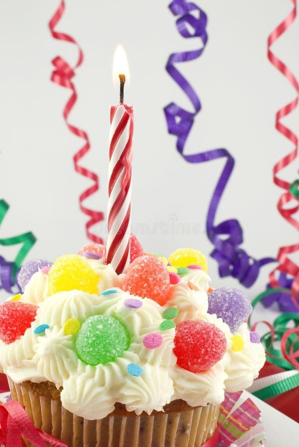 生日蜡烛五颜六色的杯形蛋糕 免版税图库摄影