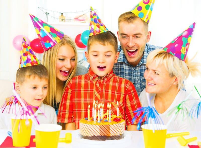 生日 小男孩吹灭在生日蛋糕的蜡烛 免版税库存图片