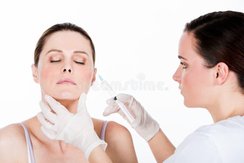 医生有botox射入妇女患者 图库摄影