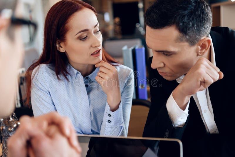 生气丈夫坐与在离婚律师` s桌后的年轻妻子 免版税库存照片
