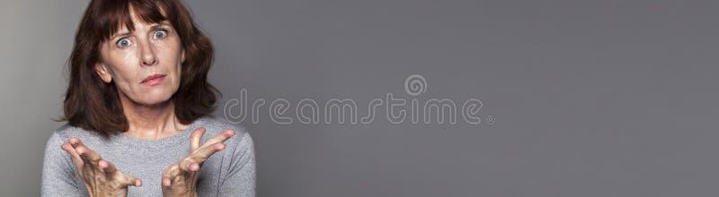 生气中部变老了表现出的妇女绝望,灰色长的横幅 图库摄影