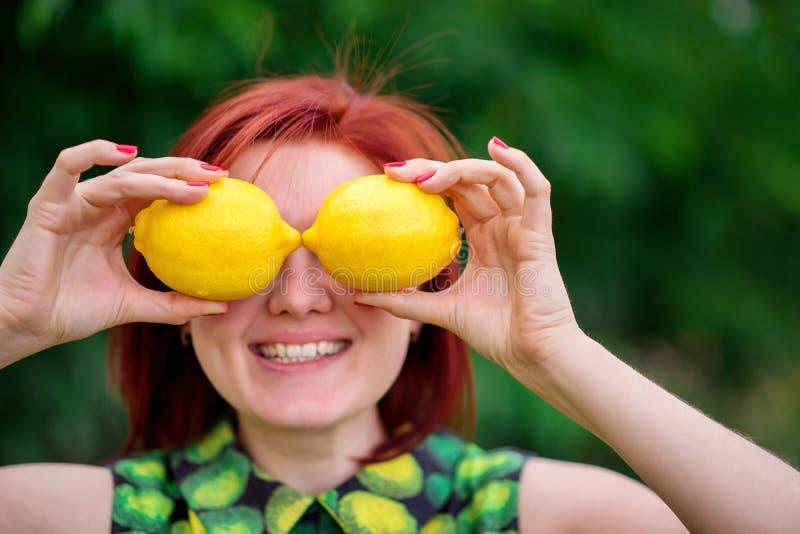 生气勃勃、健康生活方式和维生素概念:有掩藏她的在两个明亮的黄色柠檬后的红色头发的微笑的妇女眼睛 免版税图库摄影