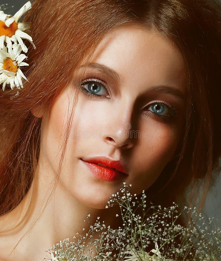 生气勃勃。浪漫红头发人妇女画象有春黄菊的 库存照片