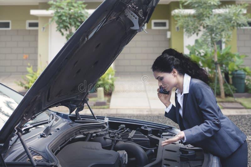 生气印地安女商人谈话在电话请求技工帮忙修理失败的汽车 免版税图库摄影