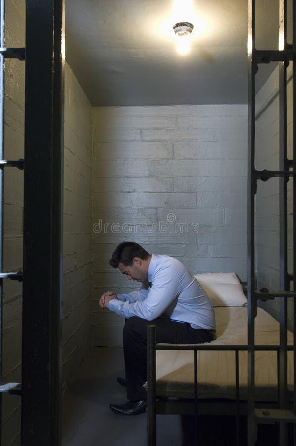 生气商人坐在监狱的床 库存图片