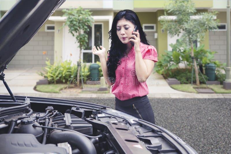 生气女商人谈话在电话请求技工帮忙修理失败的汽车 免版税库存照片