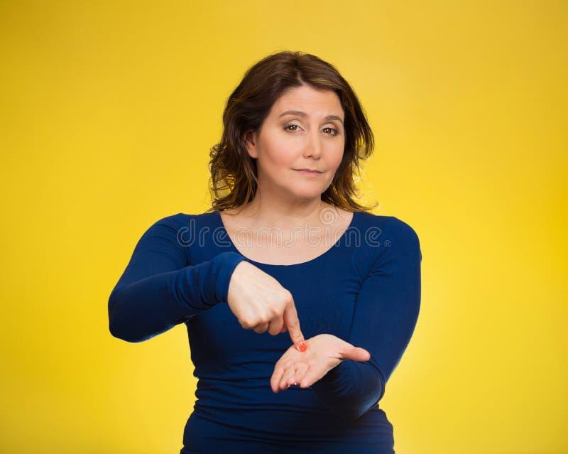 生气妇女打手势付我我的钱,在棕榈gestu的手指 免版税库存照片
