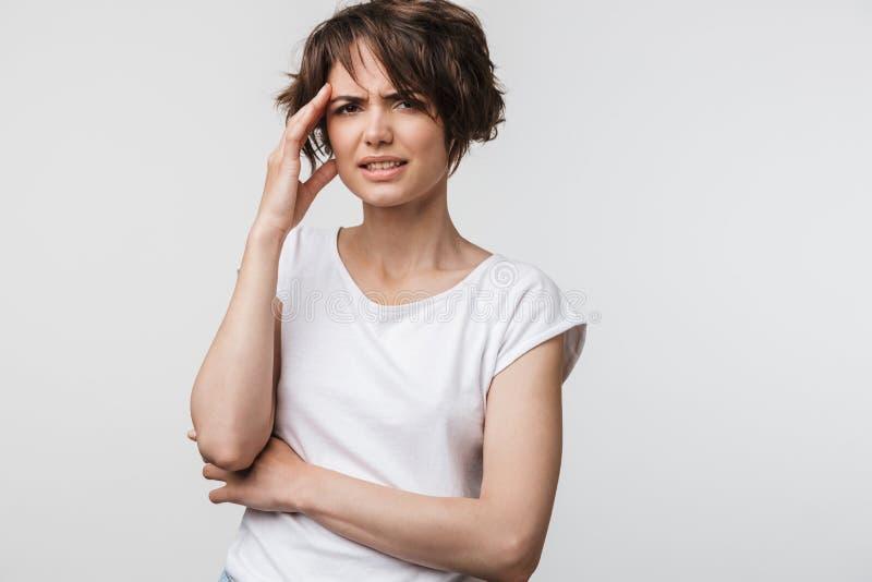 生气妇女照片有短的棕色头发的在抓住她的头和摩擦寺庙的基本的T恤杉由于头疼 免版税库存照片