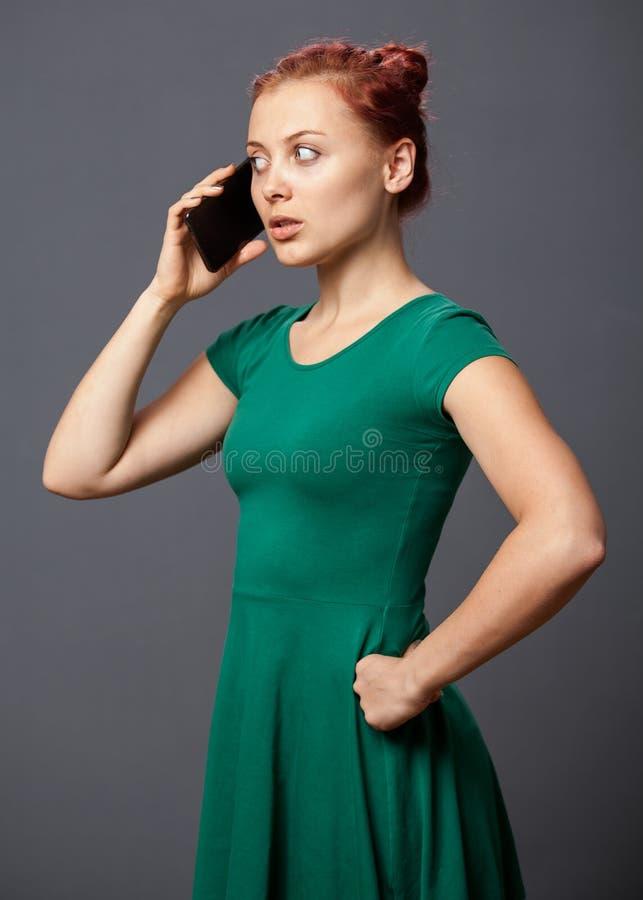 生气妇女谈话在一个手机 库存图片