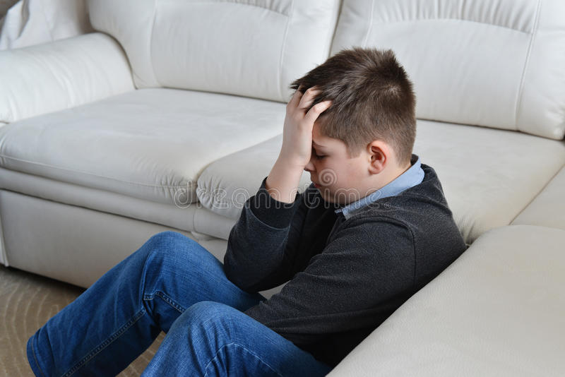 生气少年坐在长沙发附近和在手上的13年拿着他的头 库存照片