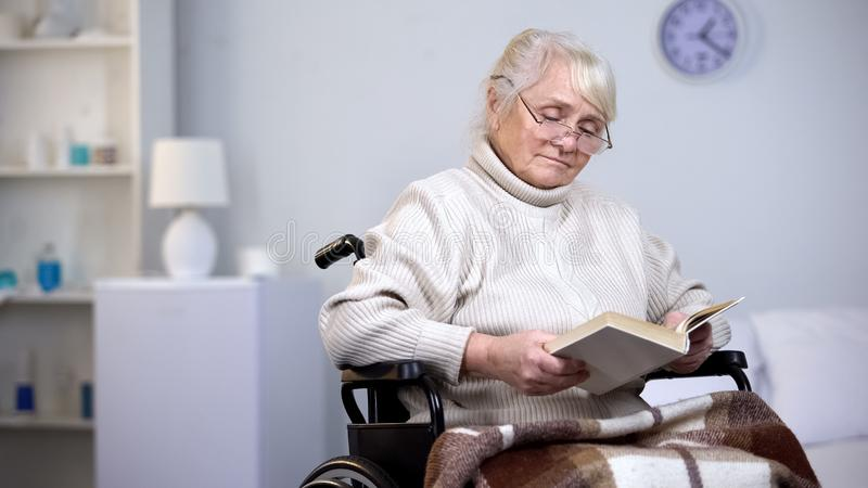 生气有残障的妇女佩带的镜片看书,在晚年的寂寞 免版税库存图片