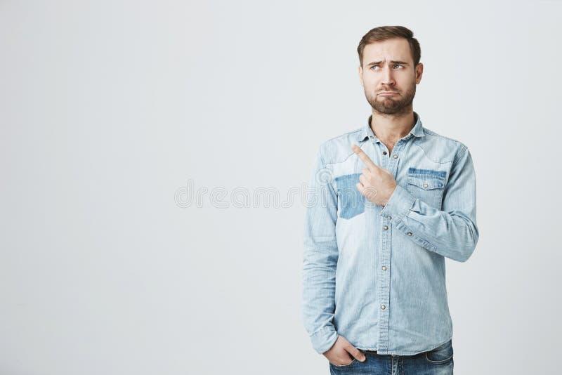 生气欧洲有胡子的哀伤地看照相机的人佩带的牛仔布衬衣皱眉的面孔,把手指指向拷贝空间  库存图片