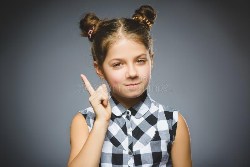 生气的和傲慢女孩与威胁在灰色背景的手指 库存图片