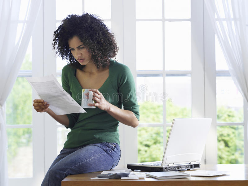 生气的妇女读书文件在家 免版税库存图片