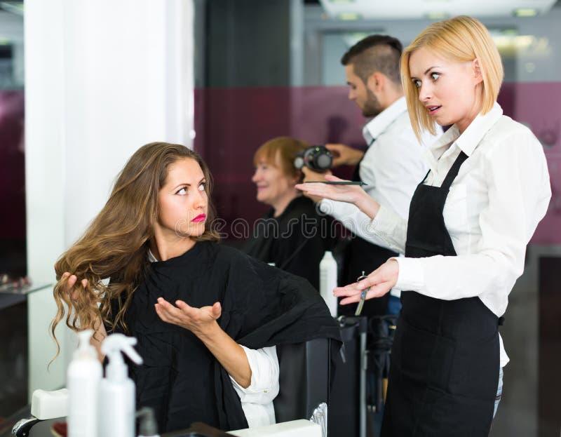 生气的客户和美发师 免版税库存图片