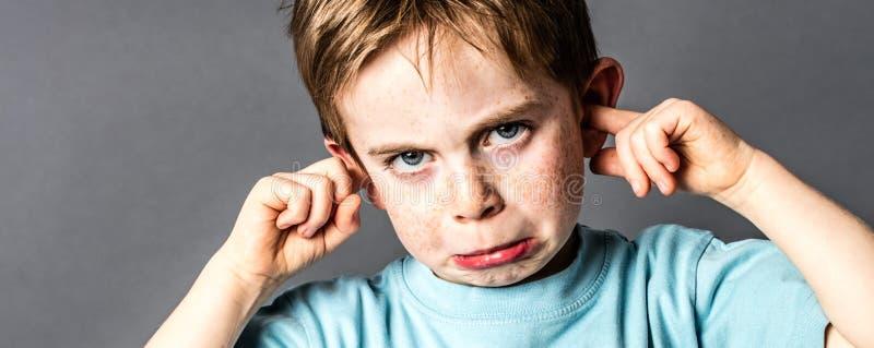 生气的小男孩特写镜头有雀斑的反对教育问题 免版税图库摄影