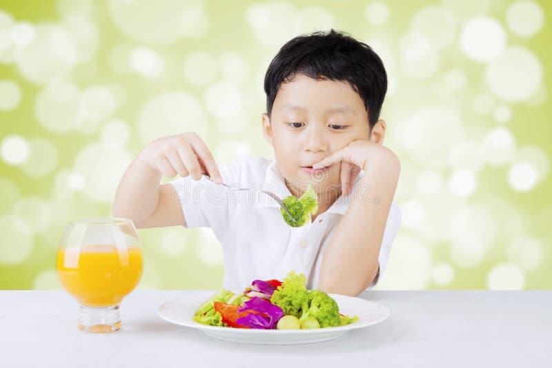 生气的男孩吃沙拉 库存照片