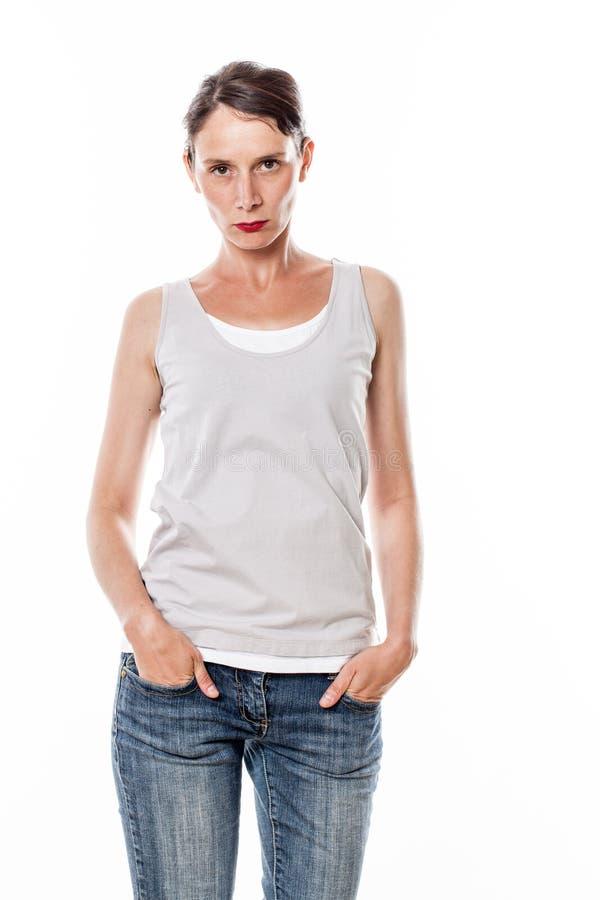 生气的美丽的少妇用在牛仔裤的手装在口袋里 库存照片