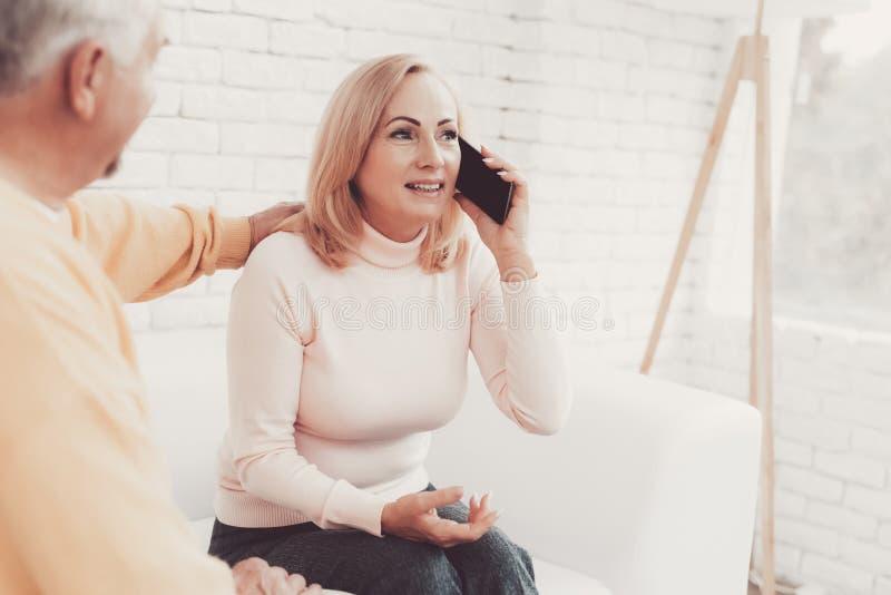 生气老妇人谈话在智能手机在老人附近 库存图片