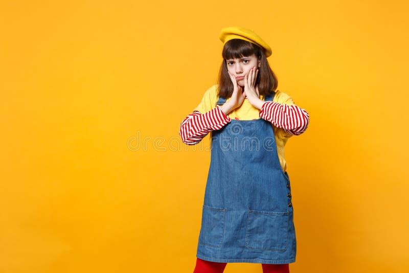 生气被触犯的女孩少年画象法国贝雷帽的,把手放的牛仔布sundress在黄色墙壁上隔绝的面颊上 图库摄影