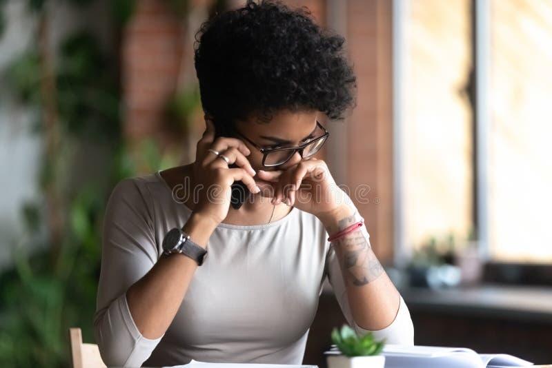 生气非裔美国人的妇女谈话在电话,坏消息 库存图片