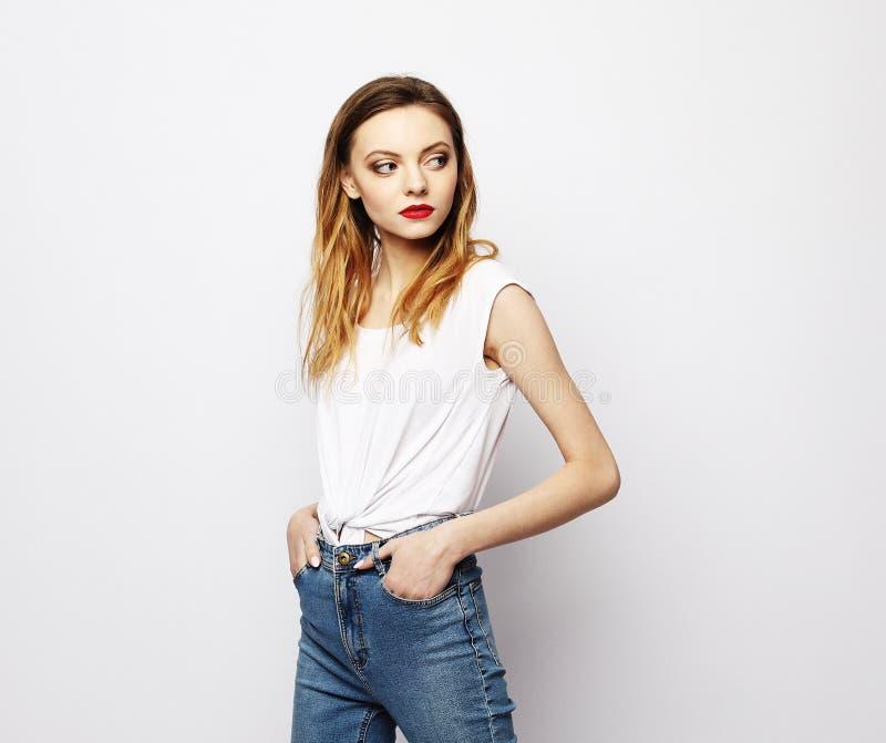 生活方式、时尚和人概念:摆在白色背景的美女佩带的便服 免版税库存图片