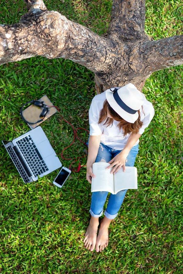生活方式人女孩享用听的音乐和读书和戏剧膝上型计算机在自然公园的草地mornin的 免版税库存照片