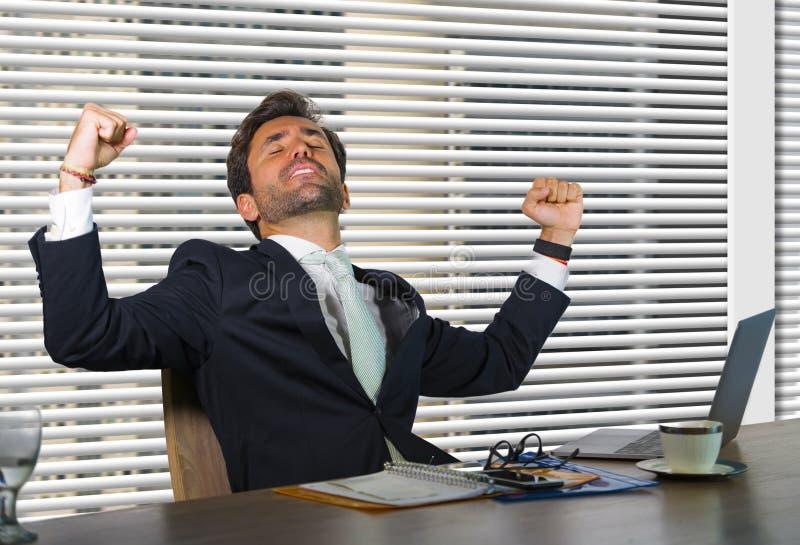 生活方式公司公司画象年轻愉快和成功商人工作激动在坐由窗口的现代办公室 免版税图库摄影