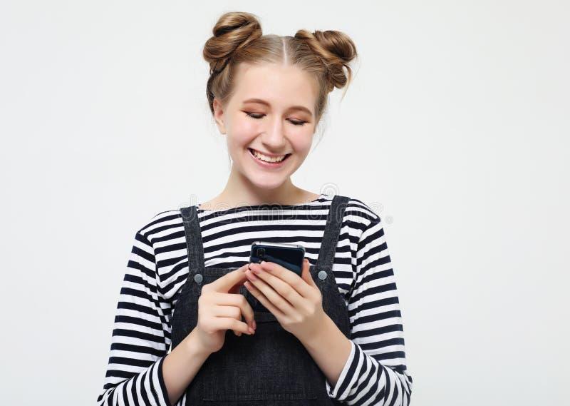 生活方式和人概念:一个愉快的年轻十几岁的女孩的画象使用手机的 库存照片
