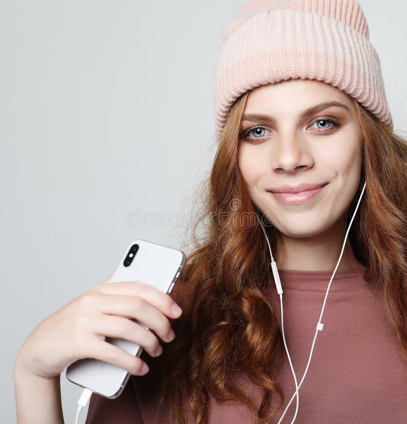 生活方式和人概念:耳机的少妇有智能手机的听到音乐的 免版税图库摄影