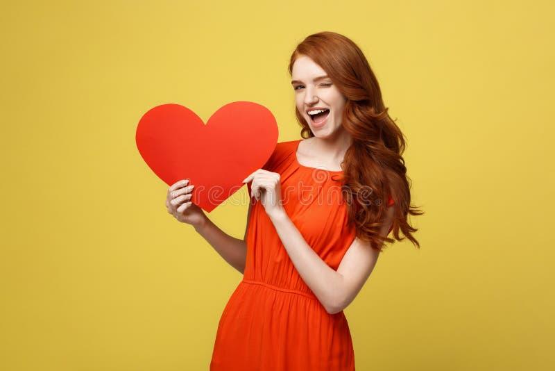生活方式和假日概念-拿着大红色心脏的橙色美丽的礼服的画象年轻愉快的红色头发妇女 免版税库存图片