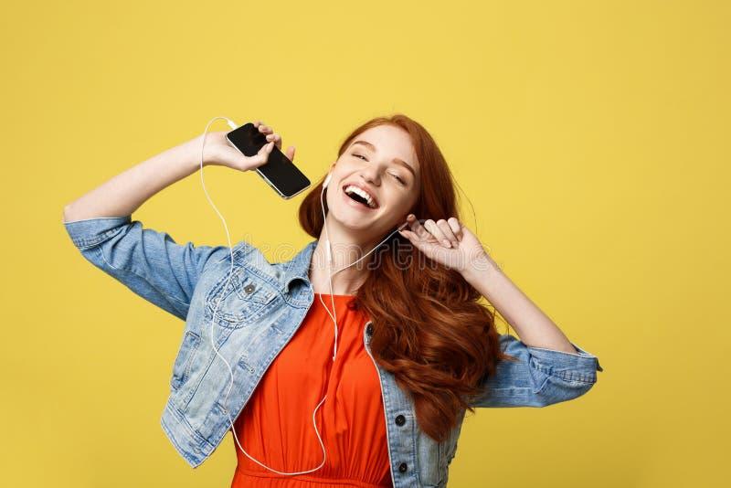 生活方式和音乐概念:耳机的美丽的年轻卷曲红色头发妇女听到音乐和跳舞在生动的 免版税库存照片